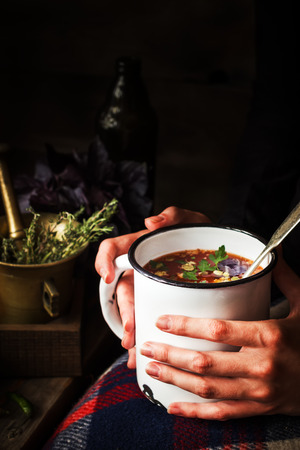 Mug with soup in female hands. Dark background, selective focus.