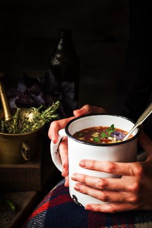 Tasse avec de la soupe dans les mains des femmes. Fond sombre, mise au point sélective. Banque d'images