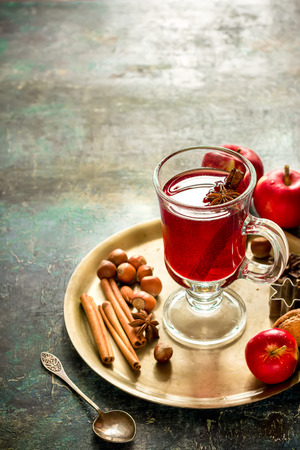 Mulled wine with apples, nuts and spices on copper tray. Blue background, place for text. Selective focus. Stock Photo