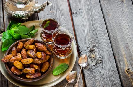 Thé à la menthe en style arabe et dates sur table en bois. Mise au point sélective