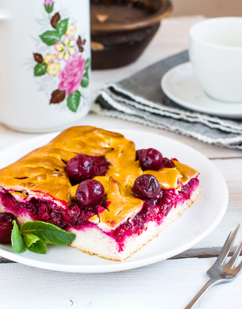Cherry pie on white plate. Wooden background. Selective focus.