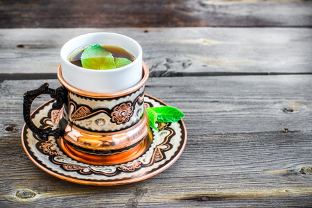Tea with mint in arab style  on wooden table. Selective focus.