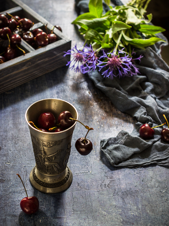Metal glass with cherry,box with sweet cherry and blue flowers on dark blue background. Vintage style. Selective focus.
