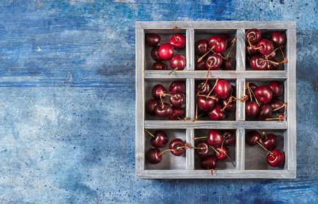 Wooden box with sweet cherry on blue background. Place for text.
