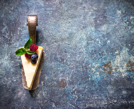 Cheesecake with berries on blue slate background. Selective focus.