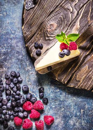Cheesecake avec des baies sur fond d'ardoises bleues. Mise au point sélective. Banque d'images