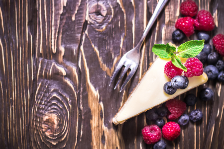 Cheesecake decorated with berries and mint. Wooden rustic background. Selective focus.Place for text.