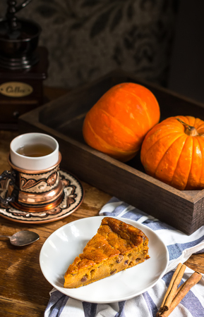Pumpkin pie and cup of tea on wooden table. Still life in vintage style. Selective focus.