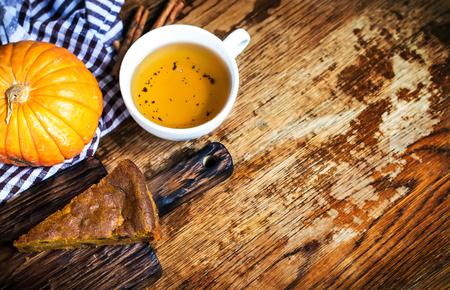 Tarte à la citrouille et tasse de thé avec de la crème fouettée sur fond rustique. Copier l'espace. Mise au point sélective. Banque d'images