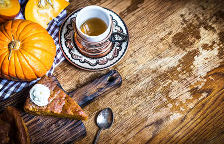 Pumpkin pie and cup of tea with whipped cream on rustic background. Copy space.Selective focus.