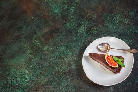 Cheesecake au chocolat avec figue sur fond d'ardoise verte. Mise au point sélective.Placez du texte.