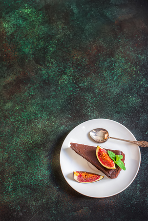 Chocolate cheesecake with fig on green slate background. Selective focus.Place for text.