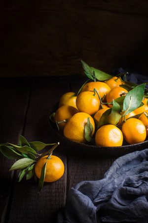 Tangerines with leaves on dark wooden table. Style rustic,selective focus.    Banque d'images