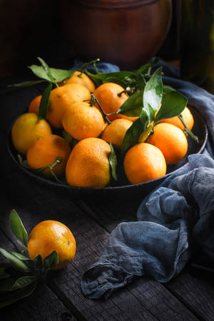 Tangerines with leaves on dark wooden table. Style rustic,selective focus.     Imagens