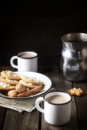 Christmas coookies in vintage plate and two mugs with hot beverage on old wooden table. Selective focus. Banque d'images