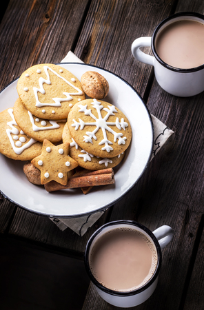 Christmas coookies in vintage plate and two mugs with hot beverage on old wooden table. Selective focus. Imagens