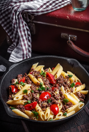 Pasta with tomatoes and meat on  dark rustic background.Selective focus.Vintage style.