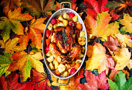 Served roasted Thanksgiving Turkey on bright autumn leaves background. Place for text. Imagens