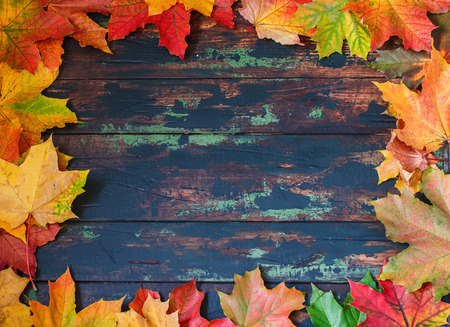 Autumn leaves frame, brown wooden background. Place for text.