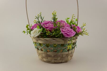 Basket with flowers on a white background. Pink artificial flowers in a wicker straw basket.