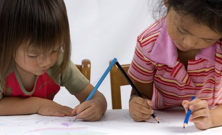 Two Sisters draw a picture together. Stock Photo - 549418