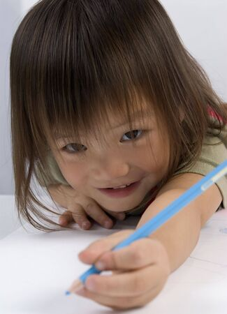 A young girl reaches forward to draw a picture Stock Photo - 549419