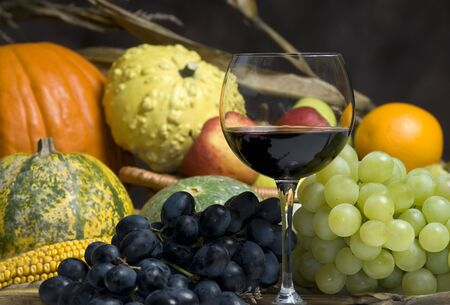 autumn harvest: A glass of wine with the fruits of the Autumn harvest.