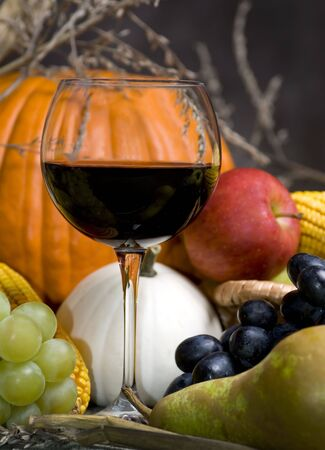 A glass of red wine with the autumn fruits photo