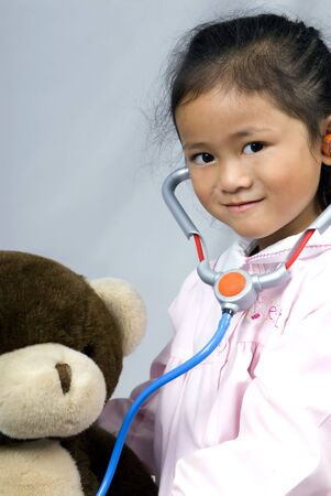 A young girl cares for her sick bear photo