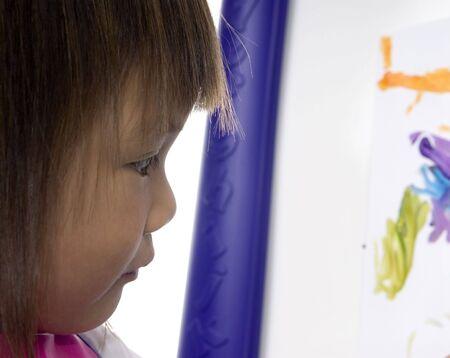 A young preschool girl concentrates as she paints a picture Banco de Imagens