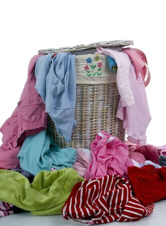 A pile of dirty clothes overflows from a young girls laundry basket photo