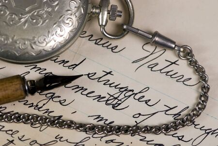 An old pocket watch and pen lay on top of a completed poem photo