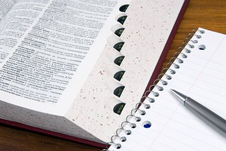 An open dictionary with a notebook and pen Stock Photo - 623884