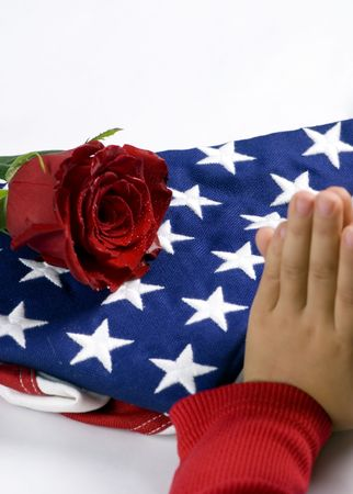 A young girl prays over a fallen loved one. In the background is the folded flag and a lone red rose which is weeping. photo