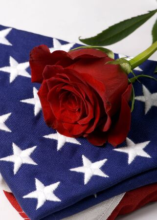 A lone red rose lying on top of a folded American flag. My hero. photo