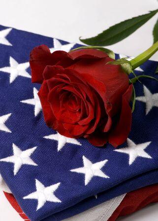 Una solitaria rosa roja situada en la cima de una bandera americana doblada. Mi héroe.