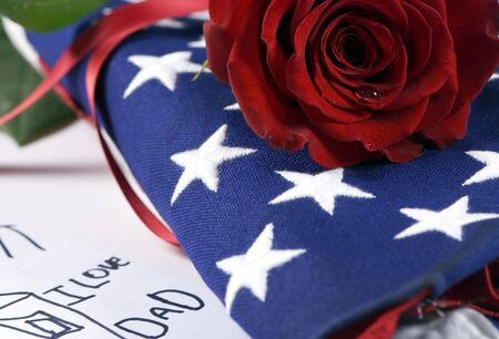 A lone red rose lying on top of a folded American flag. A single tear drop falls from the rose. I miss my daddy….my hero.  Reklamní fotografie