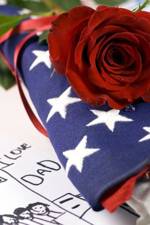 A lone red rose lying on top of a folded American flag. A single tear drop falls from the rose. I miss my daddy�.my hero.