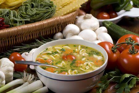 Een kommetje van verse soep, omringd door alle ingrediënten Stockfoto