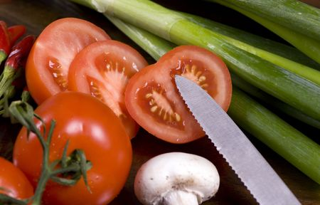 vegtables: Sliced tomatoes and an assorment of other vegtables on a table.