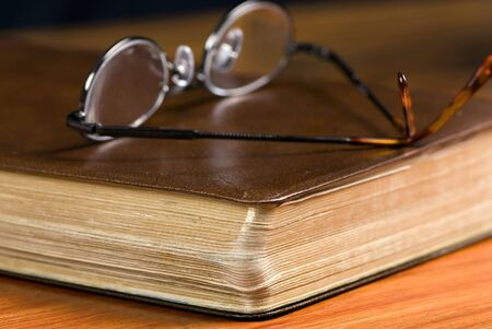 lays: A pair of glasses lays on top of a well read bible Stock Photo