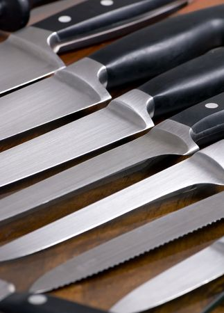 sharpen: A close up shot of high quality kitchen knives on a cutting board