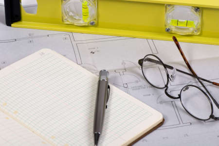 Engineering drawings laid out across a table with a calulation book and eye glasses 版權商用圖片 - 646968