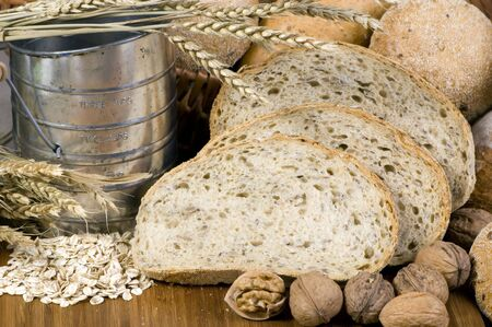 shifter: An assortment of whole grain wheat breads on a table. An old time flour shifter sits at the side.