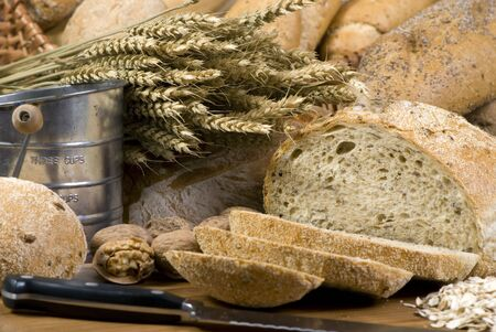 shifter: An assortment of whole grain wheat breads on a table. An old time flour shifter sits in the background an a knife in the foreground