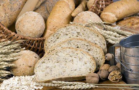 palanca de cambios: Un surtido de panes de granos enteros de trigo en una mesa. Harina de un viejo tiempo de cambios se encuentra en el lado