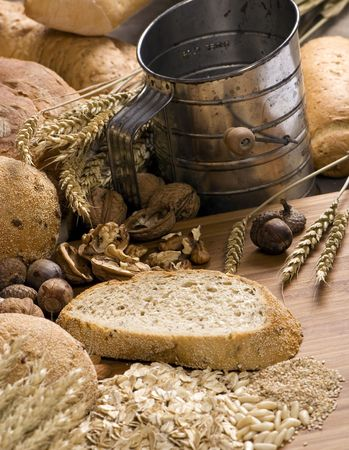 old time: An assortment of whole grain breads with mixed nuts and seeds on a table. An old time sifter sits in the background