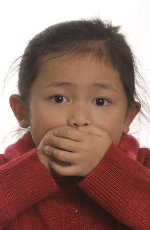 good evil: A young girl covers her mouth... Speak no Evil Stock Photo