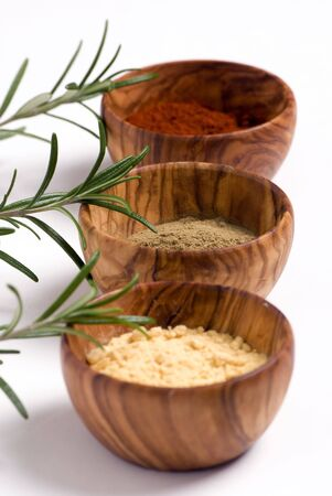 Wooden spice bowls filled with colorful spices