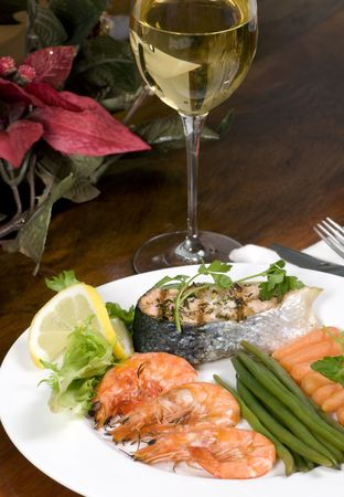 A gourmet dinner with shrimp and salmon and white wine photo